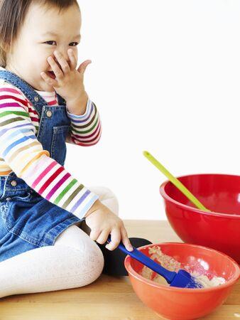 stir up: Little Asian girl mixing dough LANG_EVOIMAGES
