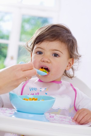 0 1 year: Small child being fed vegetables