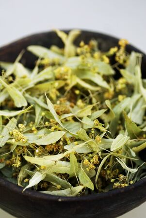 tiliae: Dried lime flowers in dish (close-up)