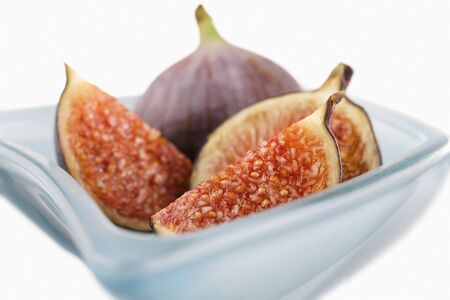 quartered: Fresh figs (whole, halved and quartered) in blue glass bowl