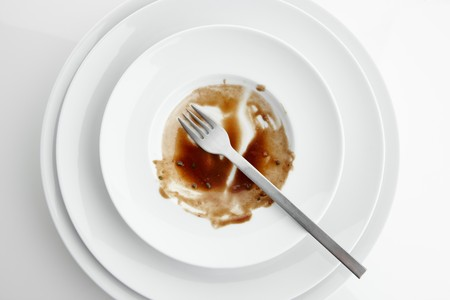 jus: The remains of sauce and a fork on a plate seen from above