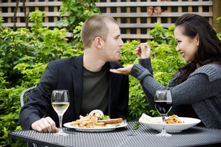 eating area: Woman feeding man with pasta