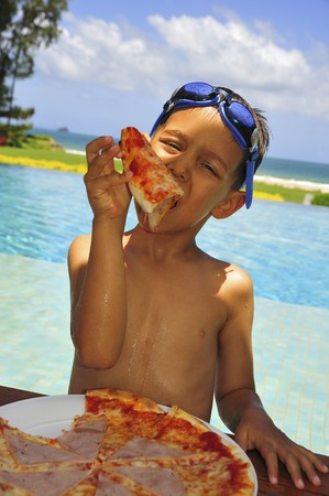 swimming goggles: Boy with swimming goggles on head eating pizza on beach