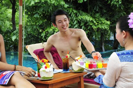 Woman serving cold, exotic fruit drinks by pool