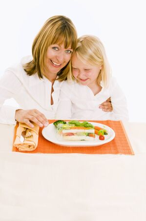 35 to 40 year olds: Mother & daughter sitting at table in front of vegetable terrine LANG_EVOIMAGES