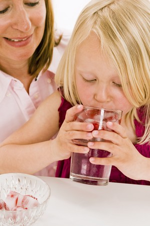 35 to 40 year olds: Girl drinking water with raspberry ice cubes LANG_EVOIMAGES