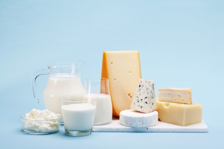 milk products: Various milk products (cheese, yoghurt, quark, milk) on a blue background
