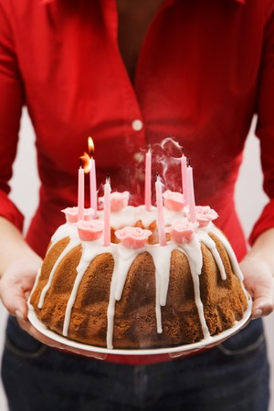 Woman holding iced ring cake with birthday candles