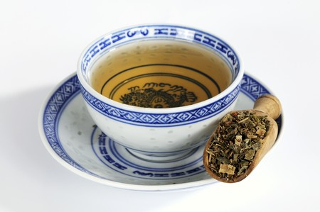 Rhubarb root in wooden scoop with tea LANG_EVOIMAGES