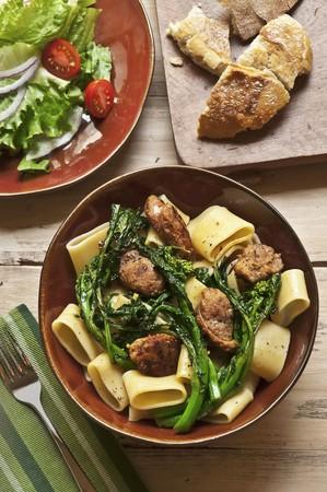 comida: Tigela de macarrão com brócolis Rabe e salsicha; Salada e pão LANG_EVOIMAGES