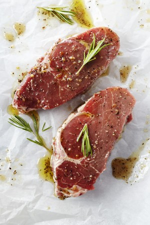 messed up: Two Raw Steaks with Marinade and Rosemary on Butchers Paper LANG_EVOIMAGES