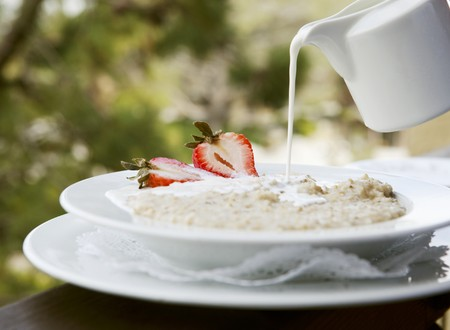 milk pouring: Milk Pouring from a Pitcher onto a Bowl of Oatmeal with Strawberries; Outdoors LANG_EVOIMAGES