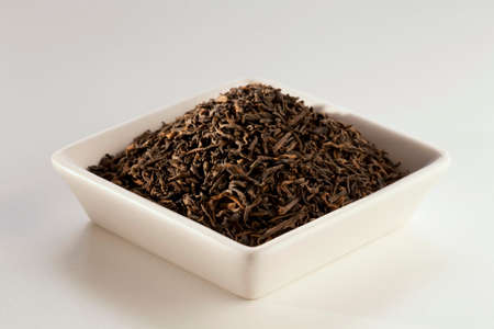 pu: Pu Erh Loose Tea in a White Dish; White Background LANG_EVOIMAGES