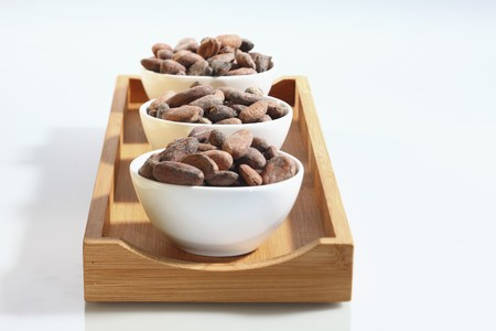 brawn: Three bowls of cocoa beans on a wooden board