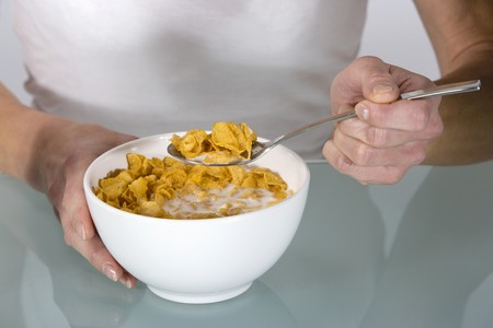 cornflakes: A woman eating cornflakes with milk
