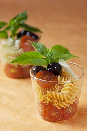 nudelsalat: Pasta salad with cocktail tomatoes, olives and basil LANG_EVOIMAGES