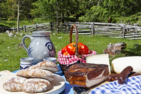 rambling: A picnic and alpine meadow with bread, bacon, cheese, sausages, tomatoes and wine LANG_EVOIMAGES