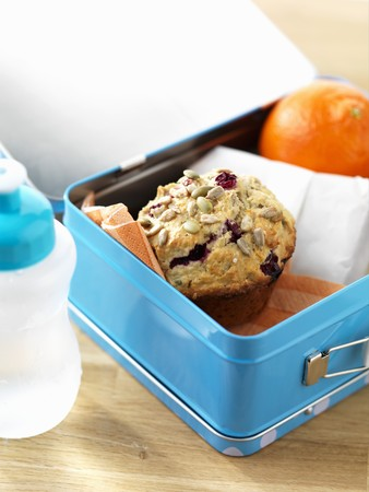 vaccinium macrocarpon: A cranberry muffin and an orange in a lunch box