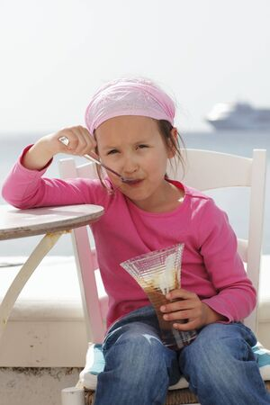 girls at the beach series: A little girl eating a chocolate ice cream sundae on a beach LANG_EVOIMAGES