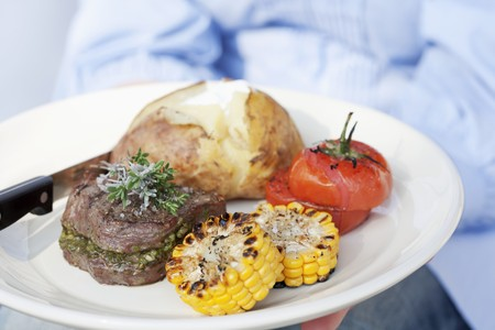 jacket potato: A person holding a plate of grilled beef medallions, a jacket potato and grilled tomatoes and corn on the cob LANG_EVOIMAGES