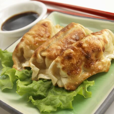 potstickers: Three Potstickers with Chopsticks and Soy Sauce LANG_EVOIMAGES
