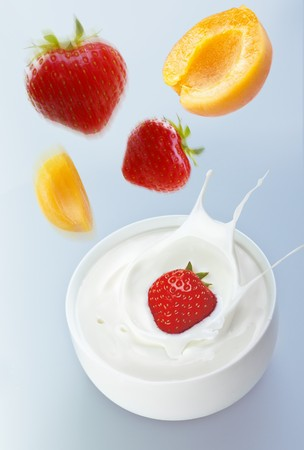 squirted: Apricots and strawberries falling into yogurt
