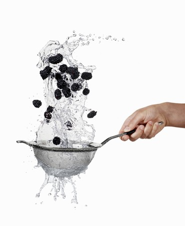 Blackberries being washed in a sieve