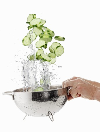 squirted: Cucumber slices being washed in a sieve