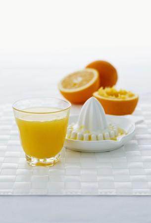 'main squeeze': A glass of orange juice, citrus squeezer and oranges