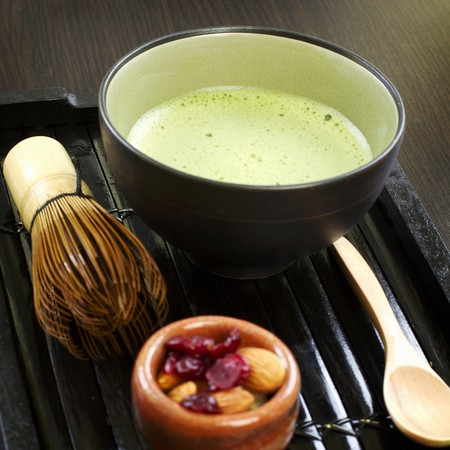 vaccinium macrocarpon: Matcha tea, a tea whisk, a teaspoon, almonds and dried cranberries LANG_EVOIMAGES