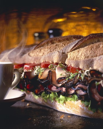 hero sandwich: A Large Sub Sandwich with a Steaming Cup LANG_EVOIMAGES