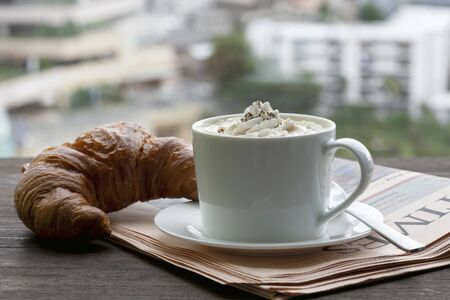 food: A cappuccino with a croissant on newspaper in front of a window LANG_EVOIMAGES