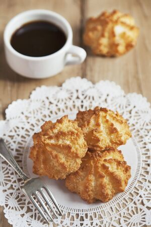 doiley: Coconut Macaroons on a Doily with a Cup of Coffee LANG_EVOIMAGES