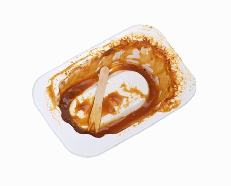leftovers: Empty container with currywurst remains in it
