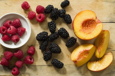 brambleberries: Fresh Raspberries, Blackberries and Peaches on Wooden Surface; From Above