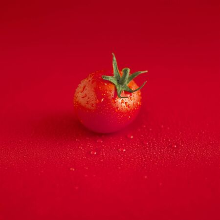 aaa: A wet tomato on a red surface