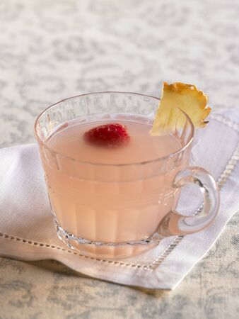 soda pops: Glass of Pink Lemonade Punch with Raspberry and Pineapple Garnish