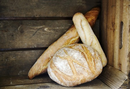 several breads: Boule, Ficelle und Baguette (French white bread) in a wooden crate