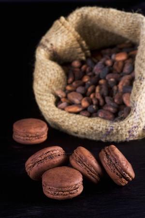 cacao beans: Macarrones de chocolate con granos de cacao en el fondo