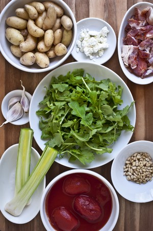 pine kernels: Bowls of Ingredients; Canned Tomatoes, Leeks, Garlic, Potatoes, Goat Cheese, Bacon, Pine Nuts and Arugula