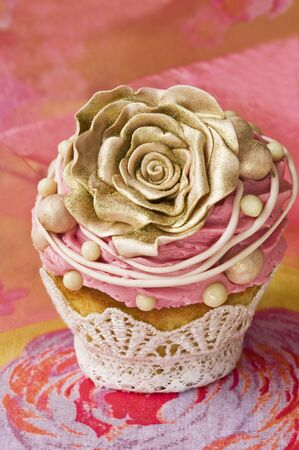 buttercream: A cupcake decorated with a gold rose and buttercream