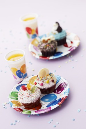 childs birthday party: Colourful cupcakes and orange juice for a childs birthday party LANG_EVOIMAGES