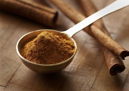 measuring spoon: Ground Cinnamon in a Measuring Spoon; Cinnamon Sticks
