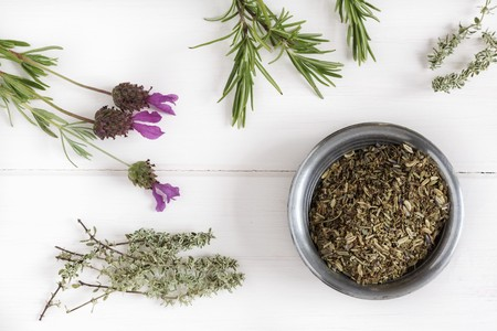 herbs de provence: Herbs de Provence in a bowl surrounded by fresh herbs LANG_EVOIMAGES