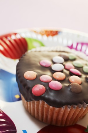 coatings: A cupcake decorated with chocolate glaze and colourful chocolate beans