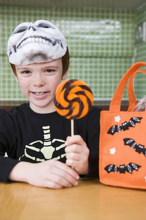 10 to 12 year olds: Little boy with trick or treat sweets