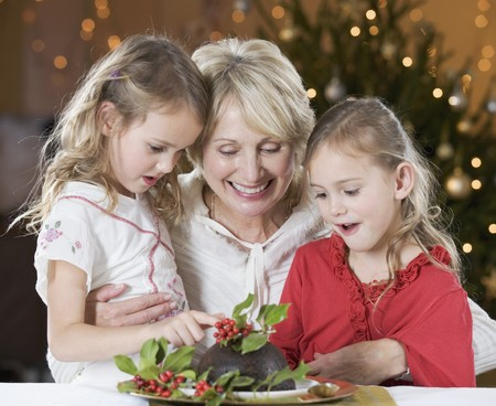 christmas pudding: A grandmother and her granddaughters looking at a Christmas pudding LANG_EVOIMAGES
