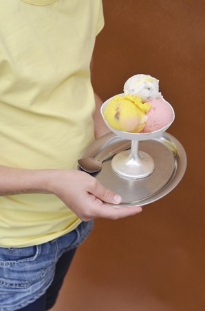 10 to 12 year olds: A girl holding a mixed ice cream sundae LANG_EVOIMAGES