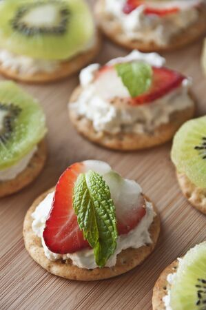 amuse: Crackers Topped with Cream Cheese, a Strawberry Slice and a Mint Leaf; Some Topped with Cream Cheese and Kiwi LANG_EVOIMAGES