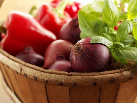 close up of onions in a basket: Red onions, peppers and basil in a wooden basket
